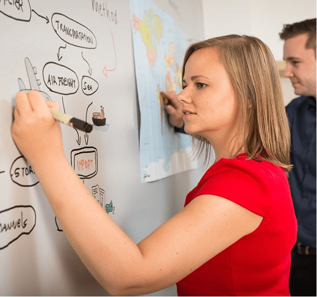 Woman writing on wall using Smarter Surfaces Whiteboard Paint Clear