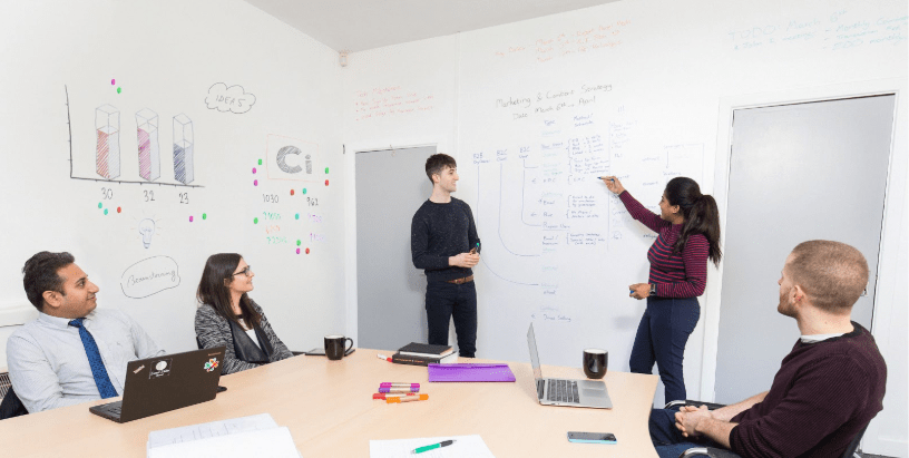 People writing on the wall during an office meeting using Smarter Surfaces Whiteboard Paint White